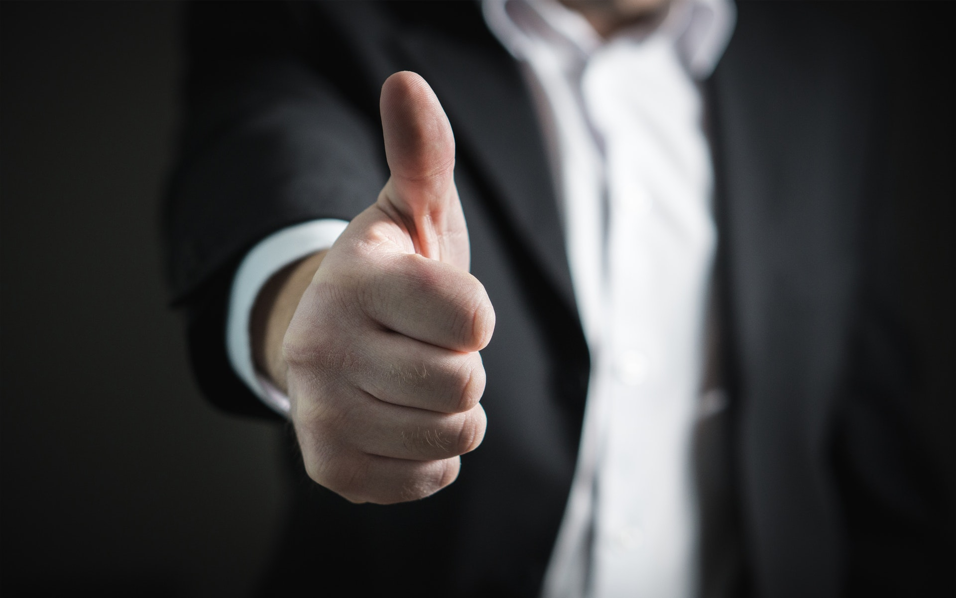 Man in suit showing thumbs up