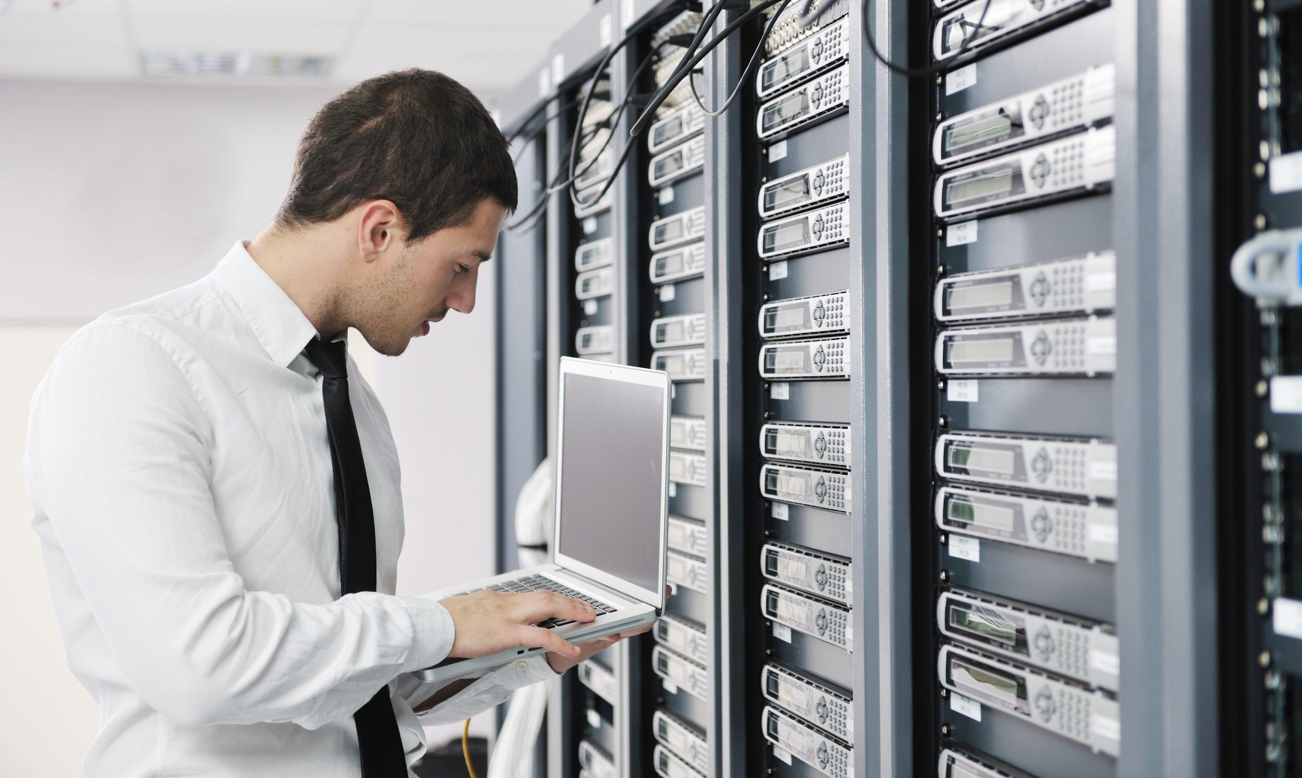 Man using laptop in server room